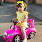 A pink boppi ride on sports car with a girl toddler in a yellow outfit sitting on and driving the car outside