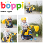 Yellow kids ride on boppi digger excavator with a toddler picking up balls on it in a garden
